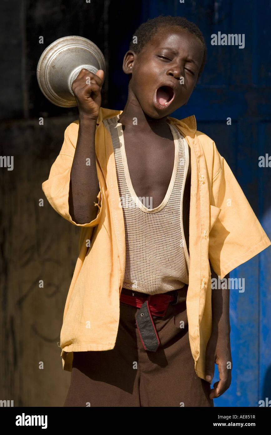 Boy ringing bell at school, Ghana - Stock Image