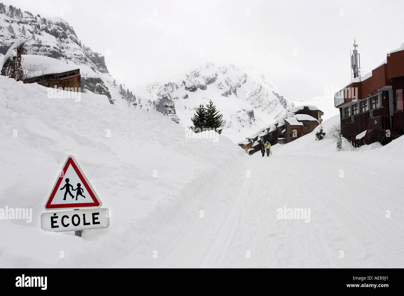 Snow covered street with school sign in Avoriaz, Morzine, Les Portes Du Soleil, Haute Savoie region, France, Europe. - Stock Image
