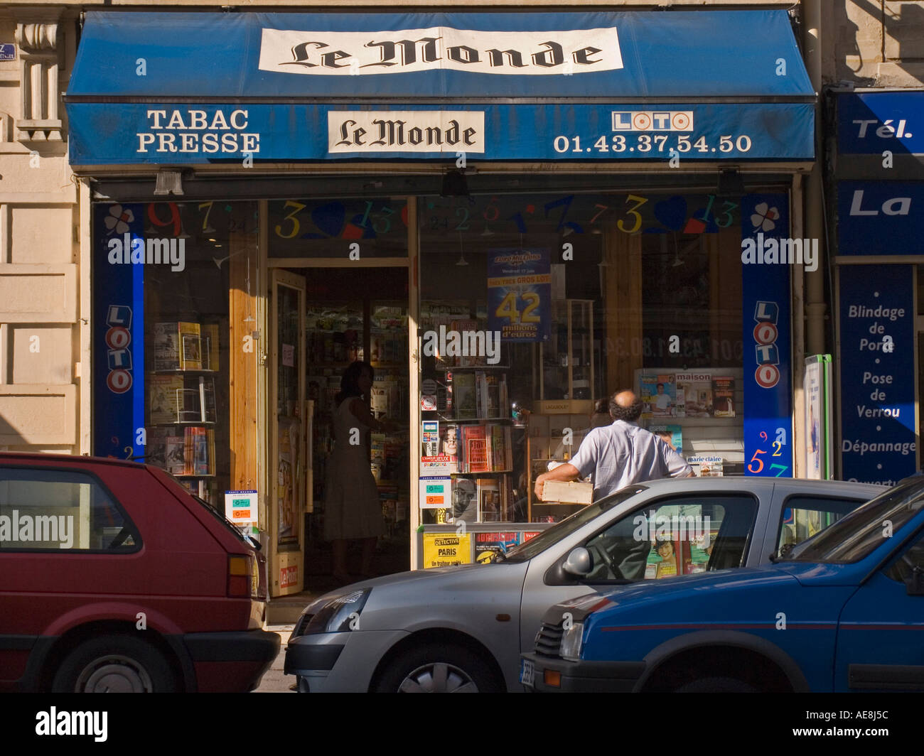 Man looking in window of Tabac and Presse shop on Rue Claude Bernard Paris France - Stock Image