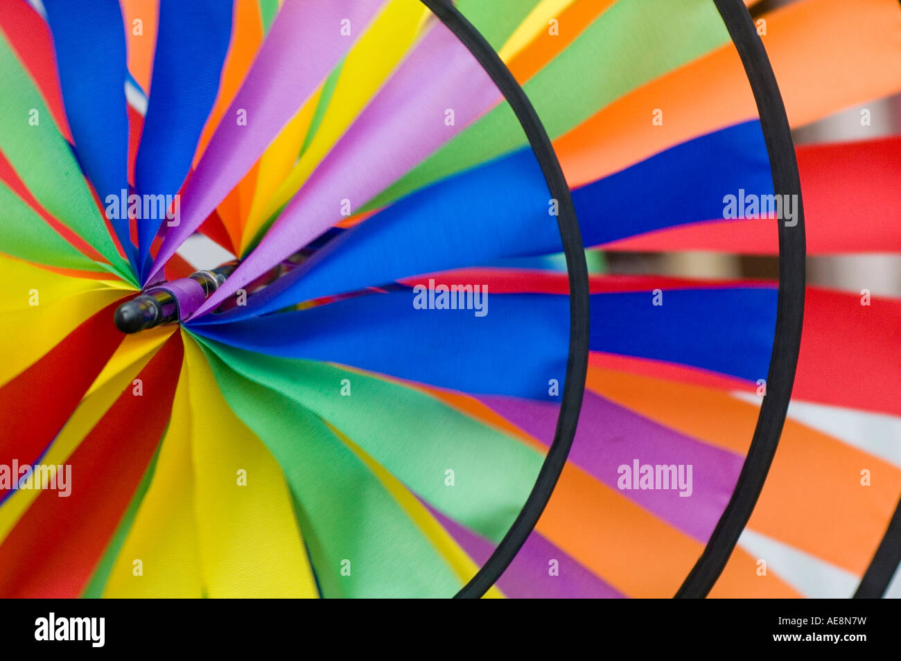 Windmill II. A spiral weather vane or wind vane made of colorful strips of cloth and sprockets - Stock Image