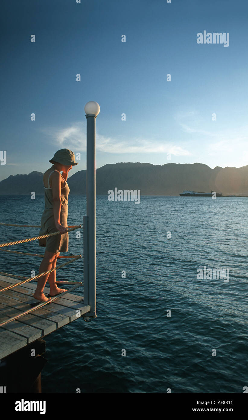 Woman on a jetty peering at the fish at sunset Red Sea coast at Nuweiba Sinai Egypt Vacation photograph Middle East - Stock Image