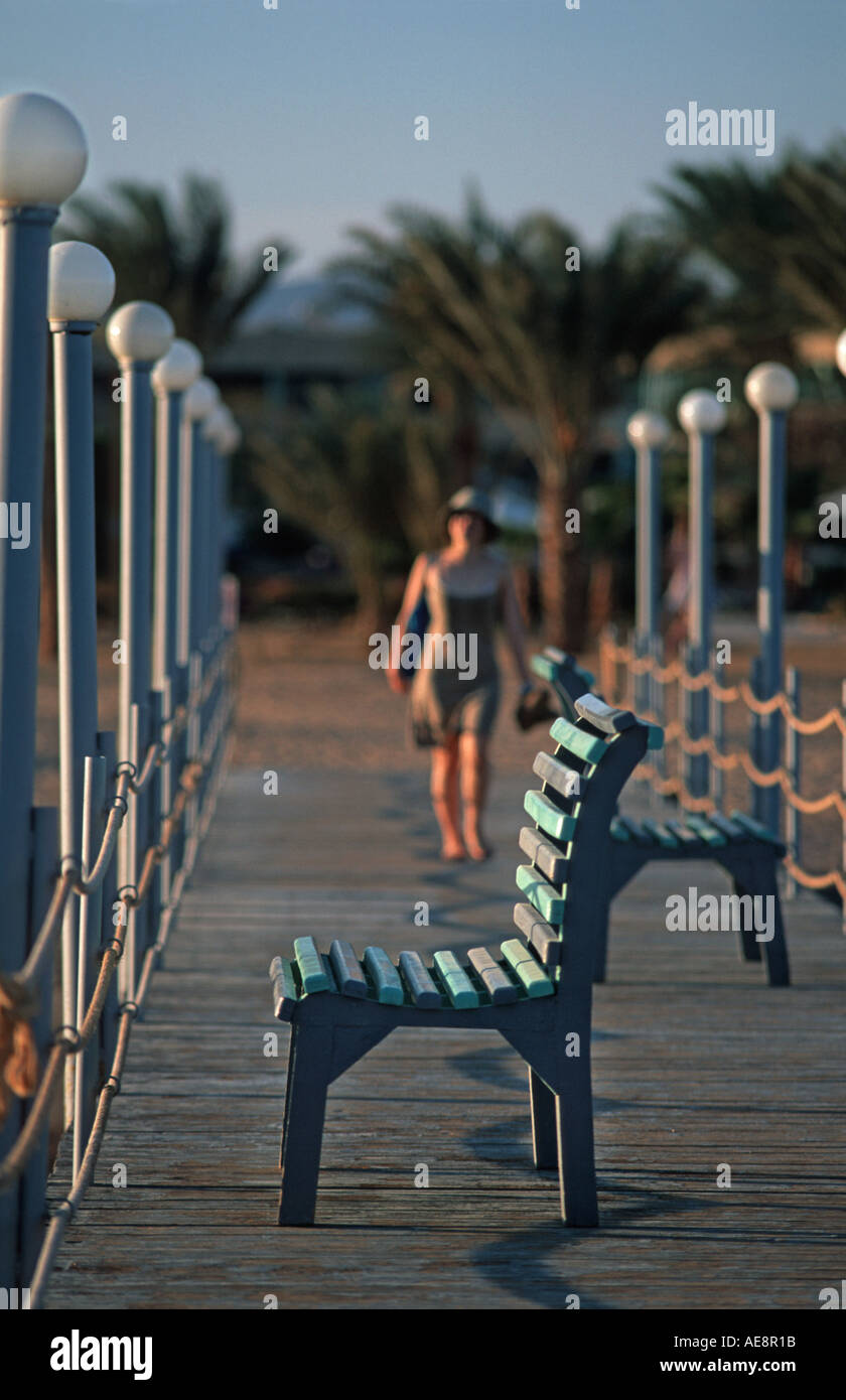 Woman walkign towards an empty seat on a jetty Red Sea coast at Nuweiba Sinai Egypt Vacation photograph Middle East Stock Photo