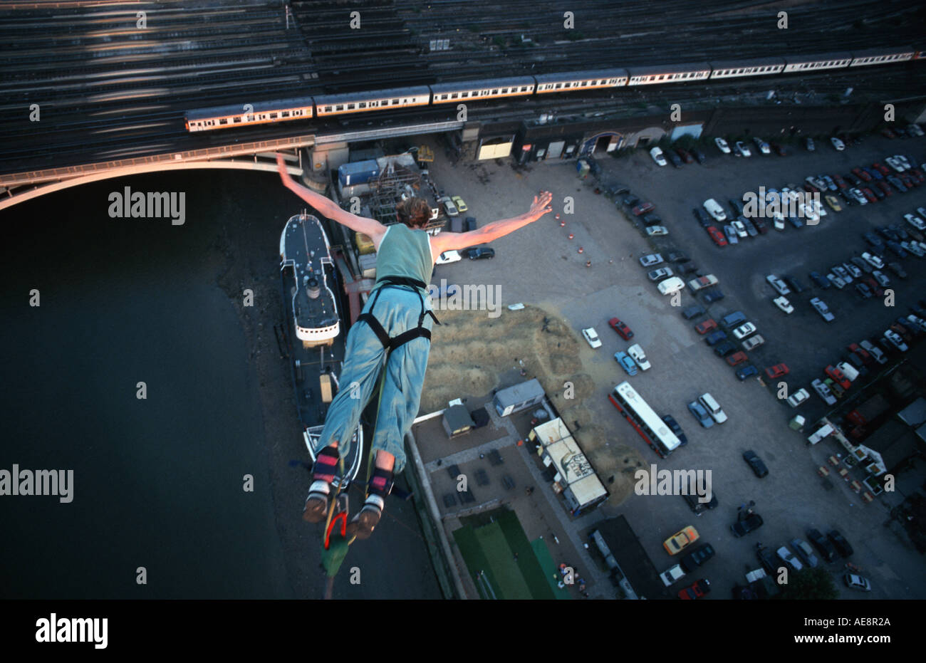 Bungie jumping from a crane high above the river Thames London England - Stock Image