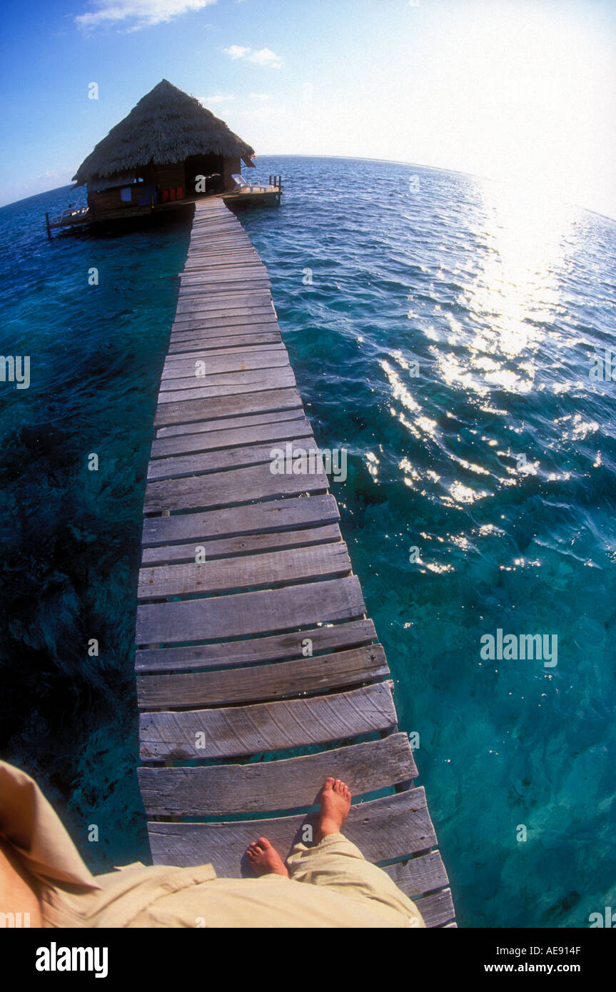 Feet and boardwalk leading towards over water bungalow Belize Caribbean Model and property released image - Stock Image