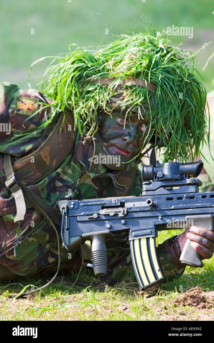 Wide eyed camoflaged British Army infantry man on excercise with SA-80 assault rifle reaching for grenade - Stock Image
