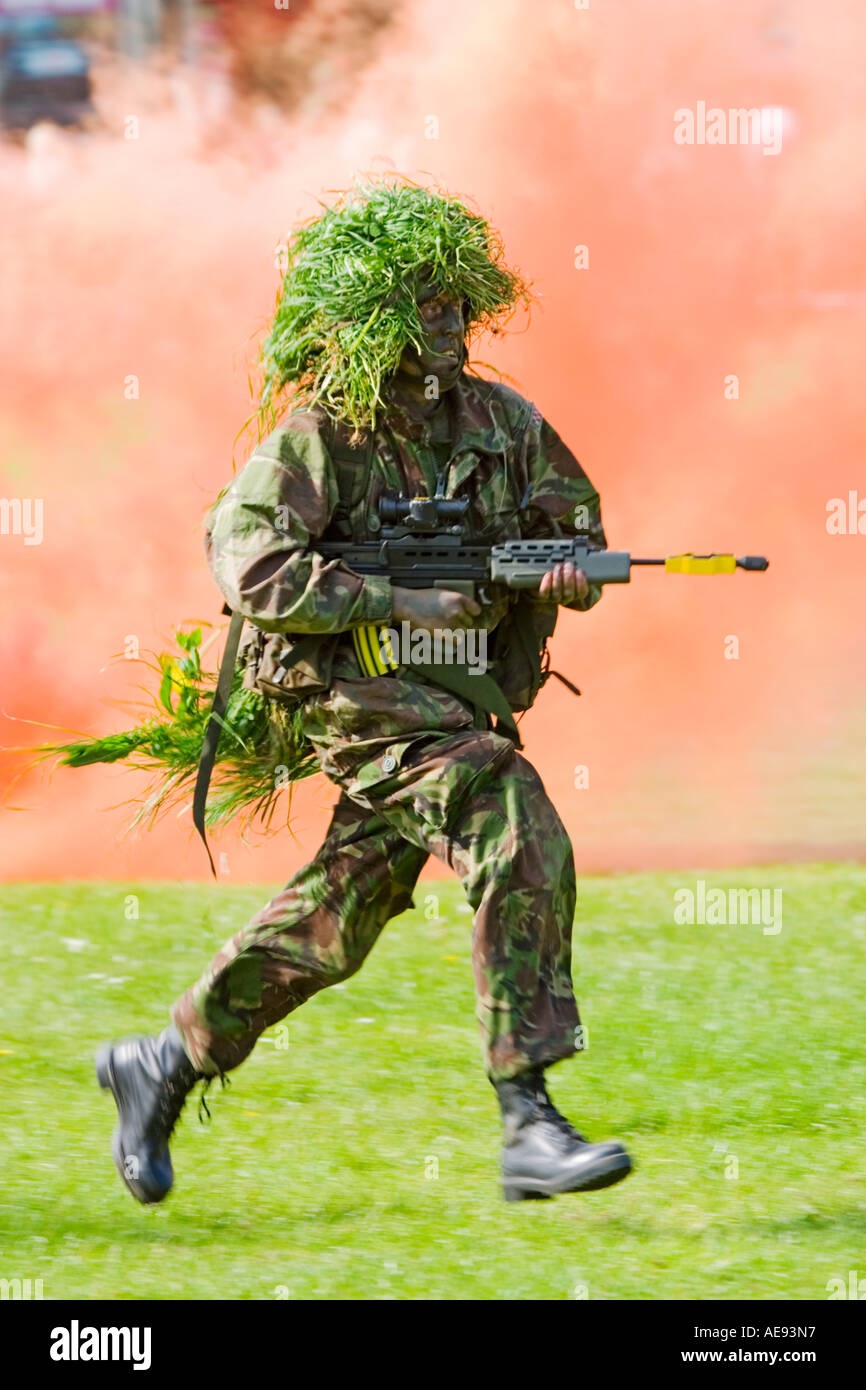 British Army infantry man on excercise with SA-80 assault rifle with orange smoke from grenade in background - Stock Image