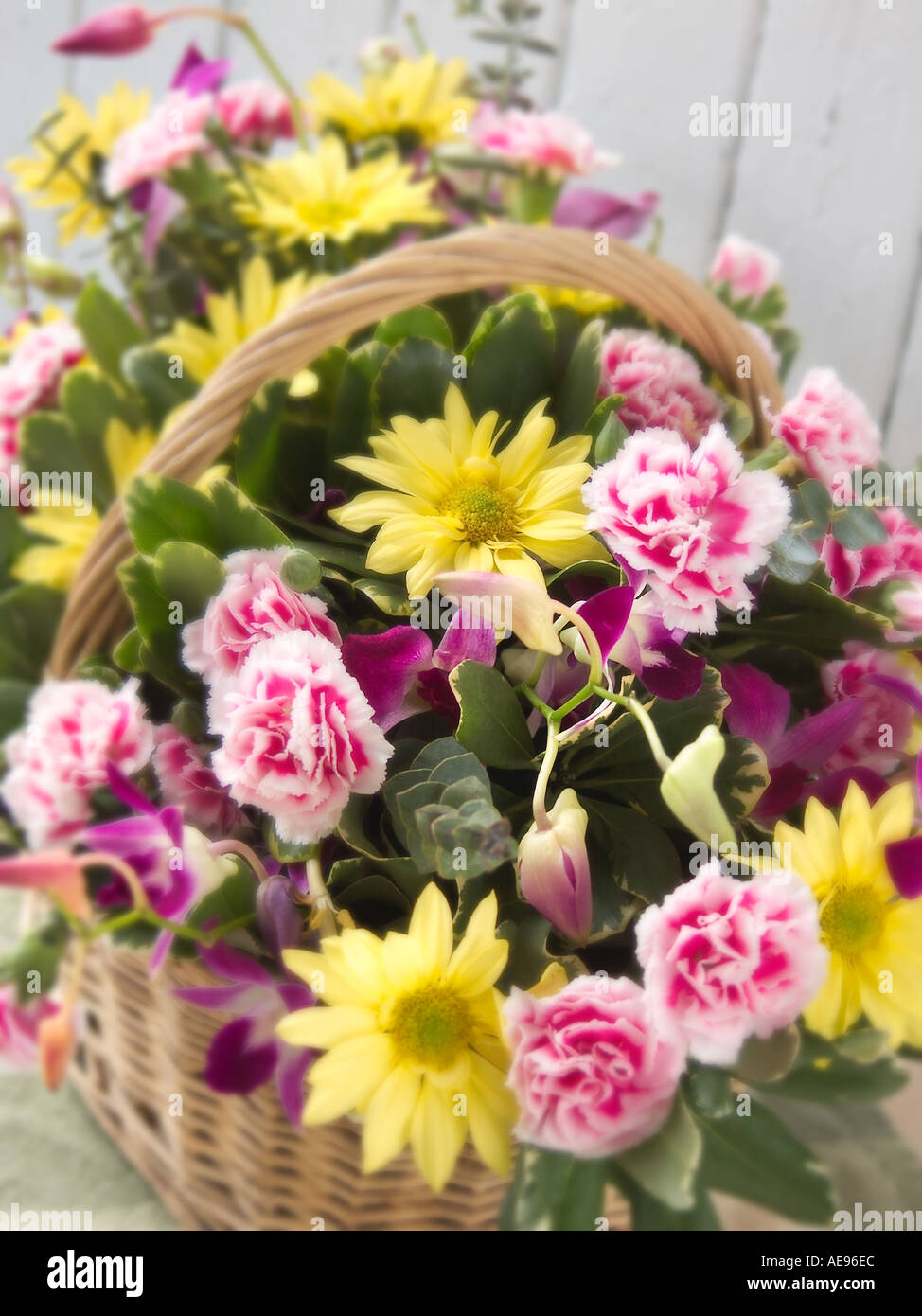 Arrangement Of Pink And Yellow Spring Flowers In Basket Against