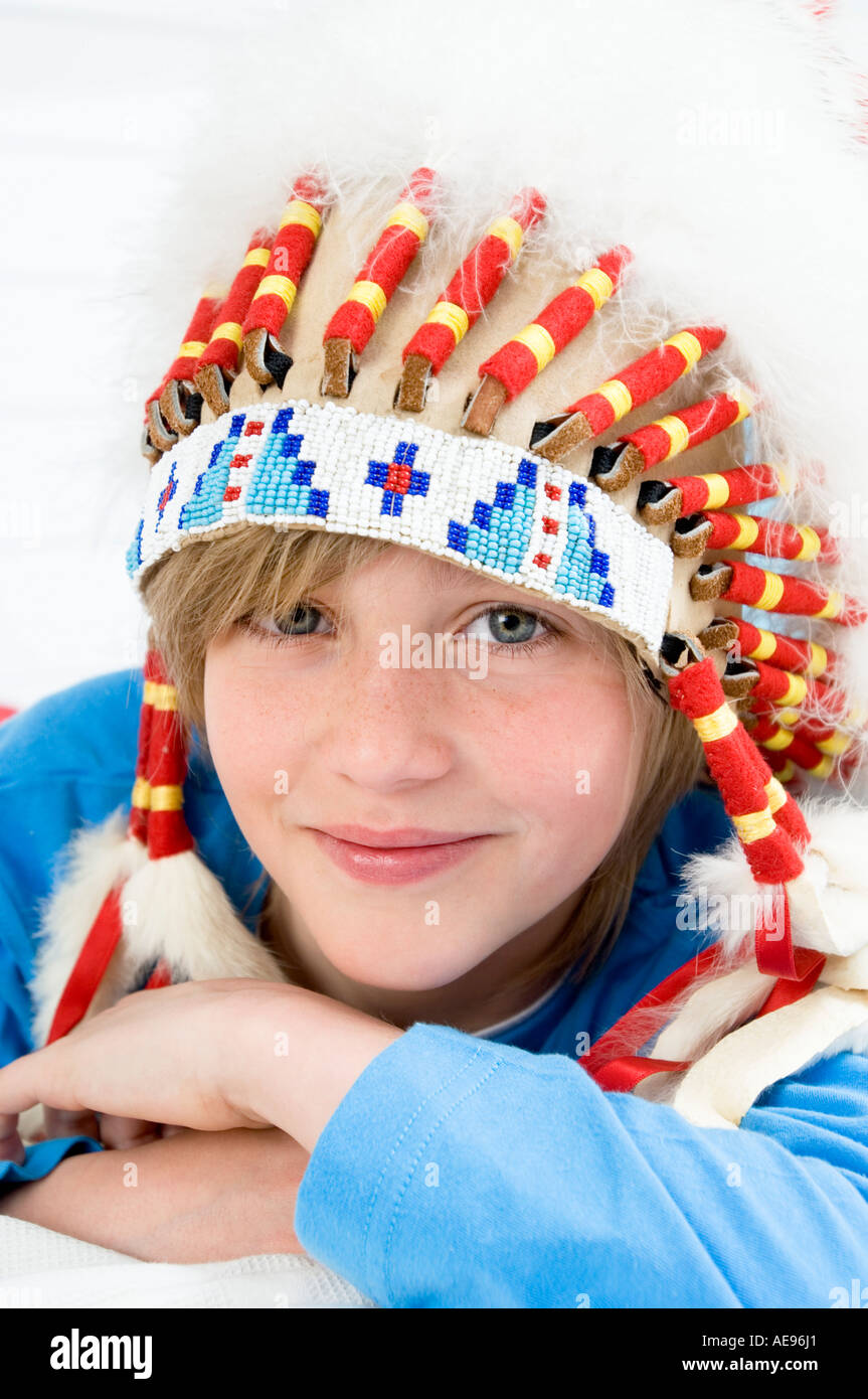 Portrait of a young boy looking at the camera, with indian headdress Stock Photo