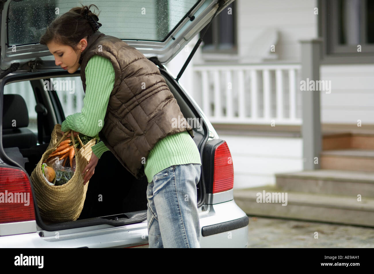 Young woman taking a shopping basket out of a car trunk - Stock Image