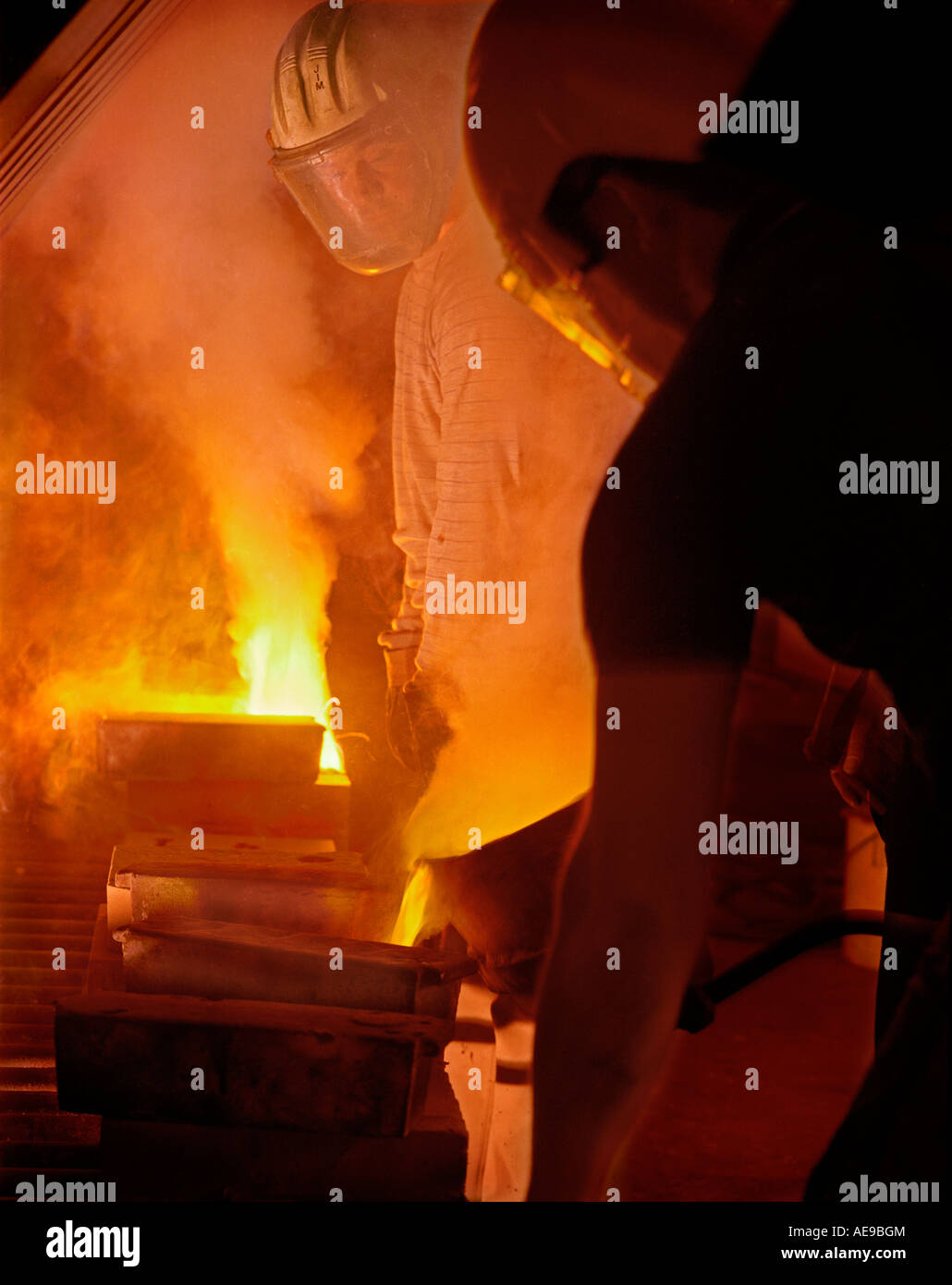 Bronze foundry men pouring molten bronze into moulds in smokey firey foundry - Stock Image