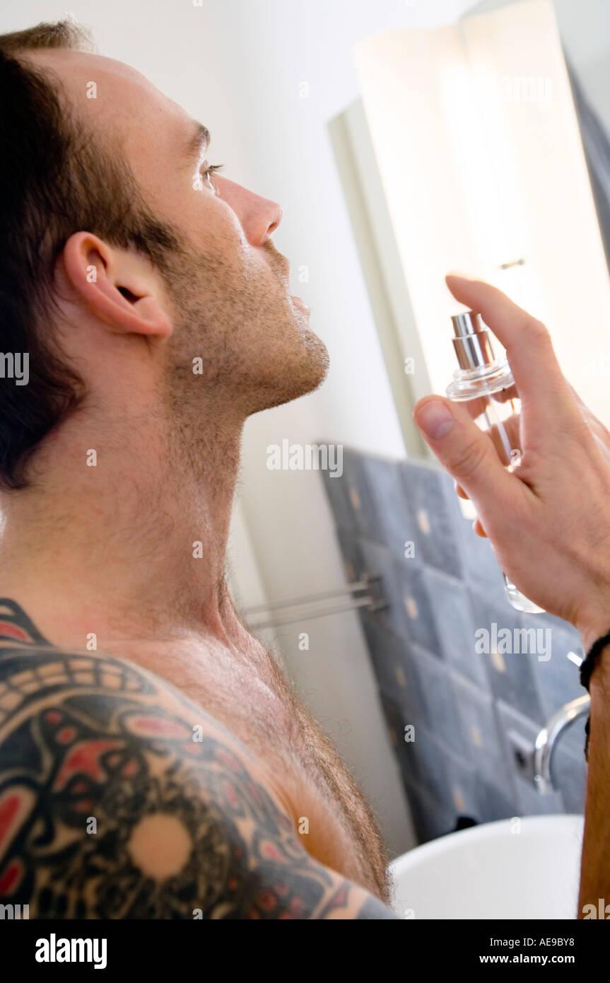 Tattooed man, barechested, spraying perfume in bathroom - Stock Image