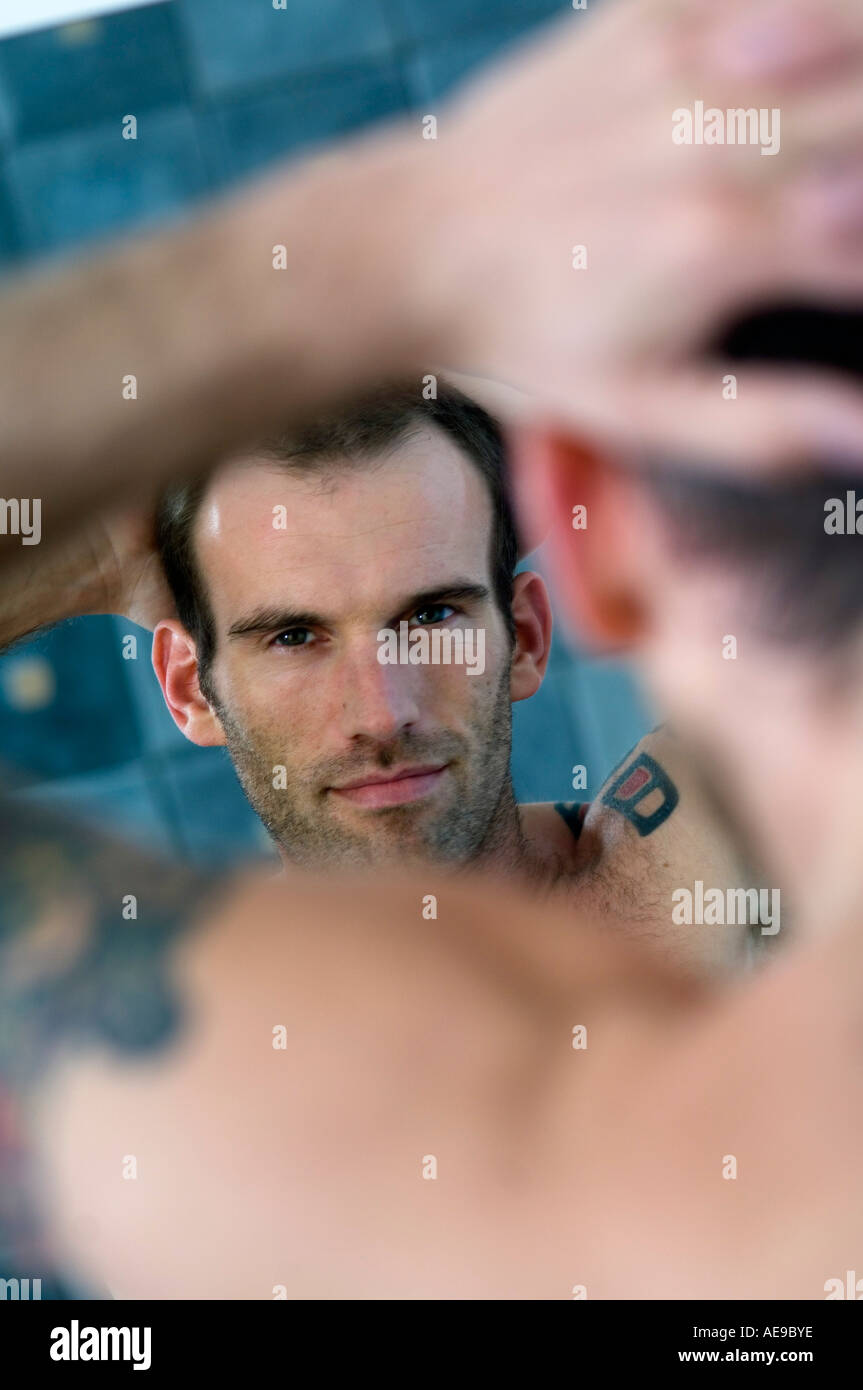 Tattooed man, barechested, looking in bathroom mirror - Stock Image