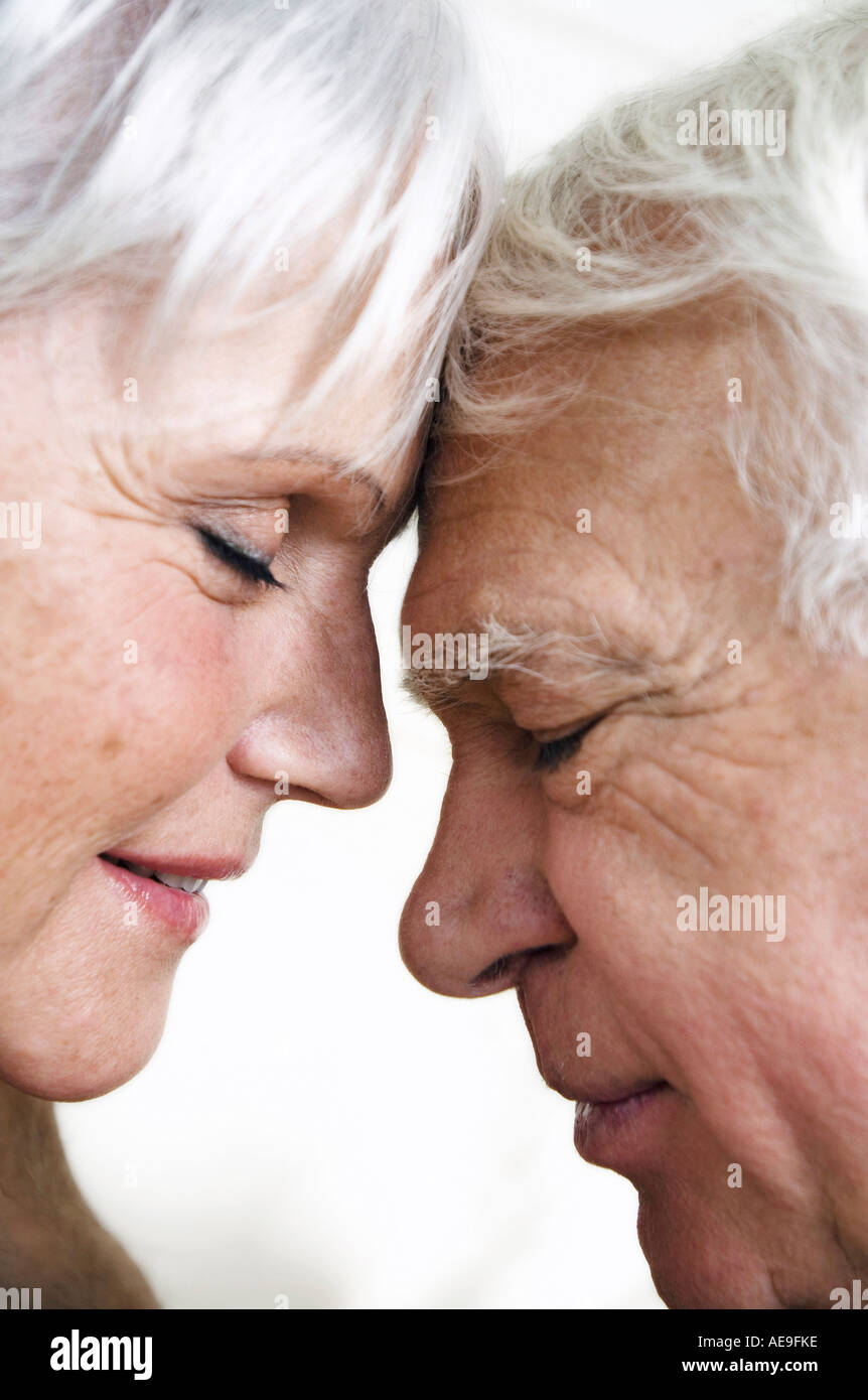 Senior couple face to face, eyes shut, close-up - Stock Image