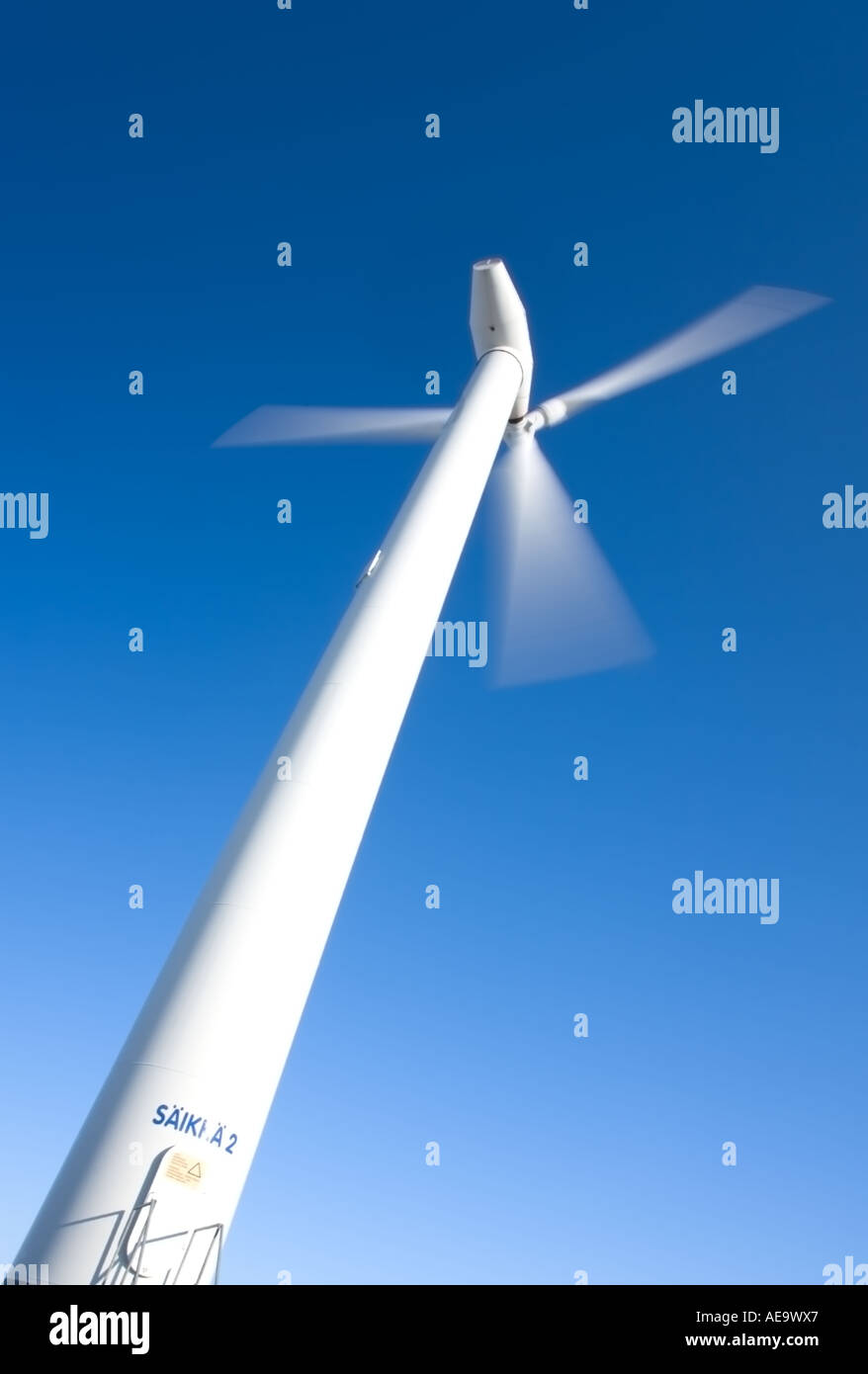 Spinning wind power plant rotor and pylon against clear blue sky - Stock Image