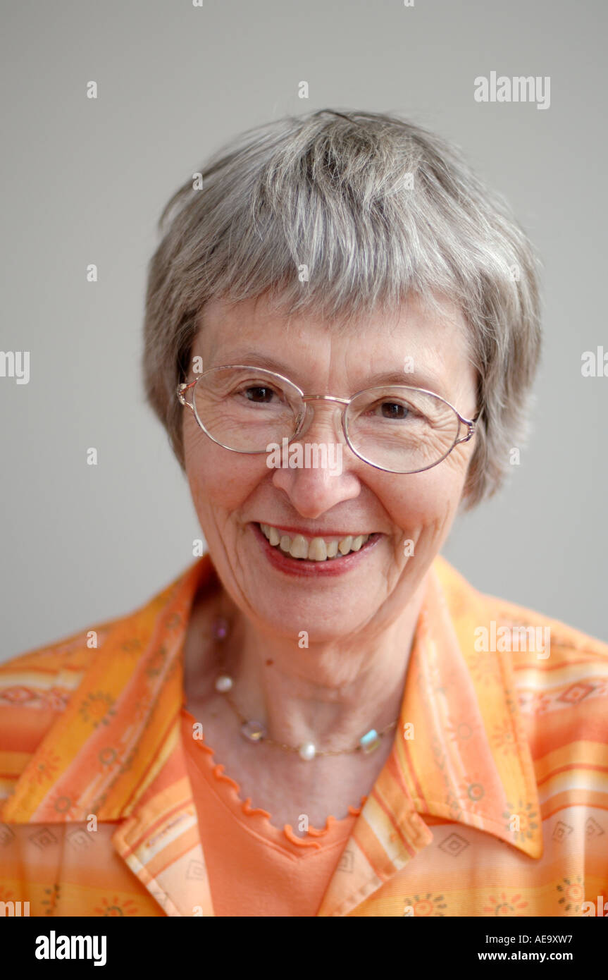 Studio portrait of elderly woman with glasses smiling at camera - Stock Image