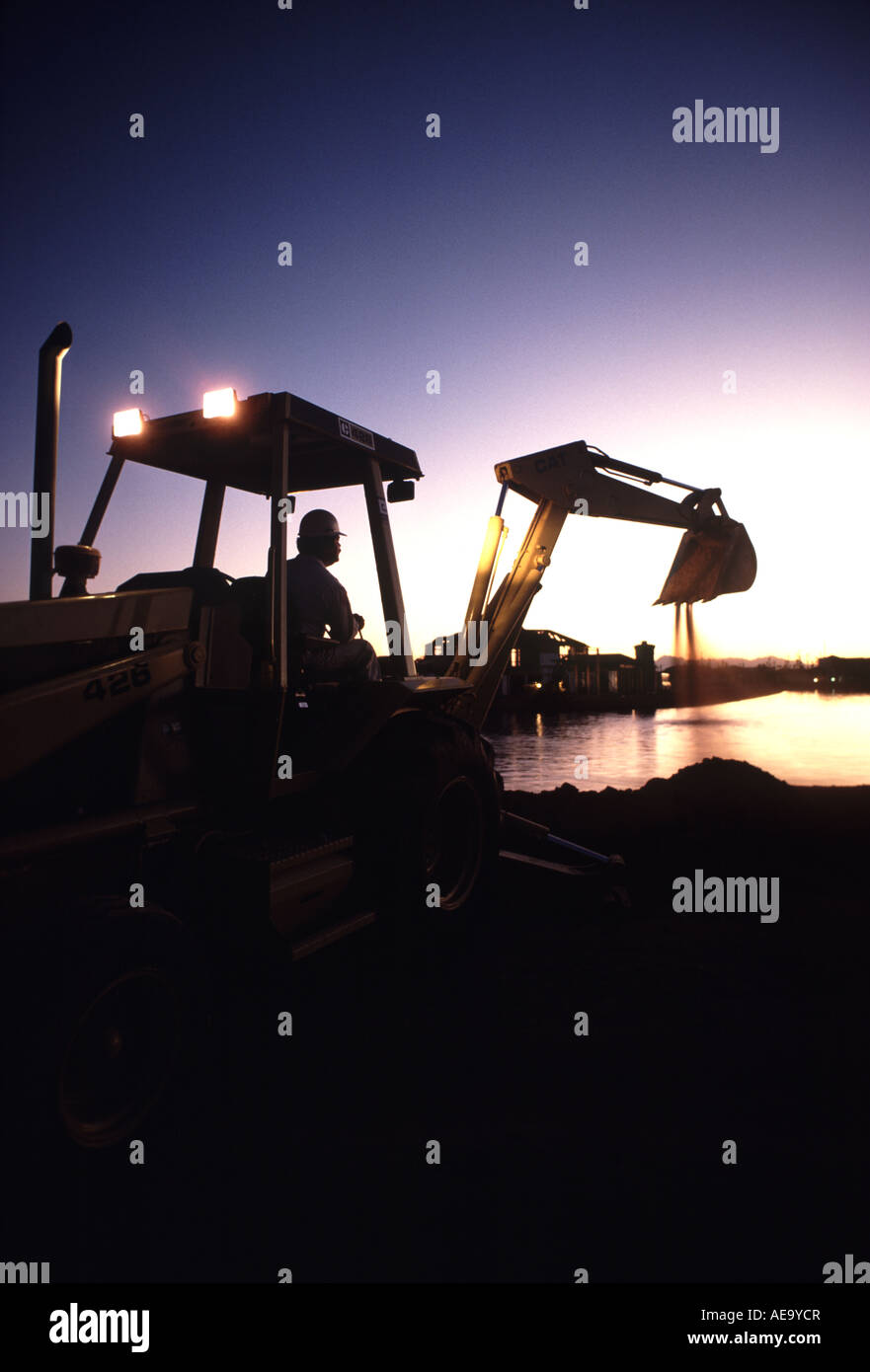 A silhouette of a man operating a backhoe at sunrise - Stock Image