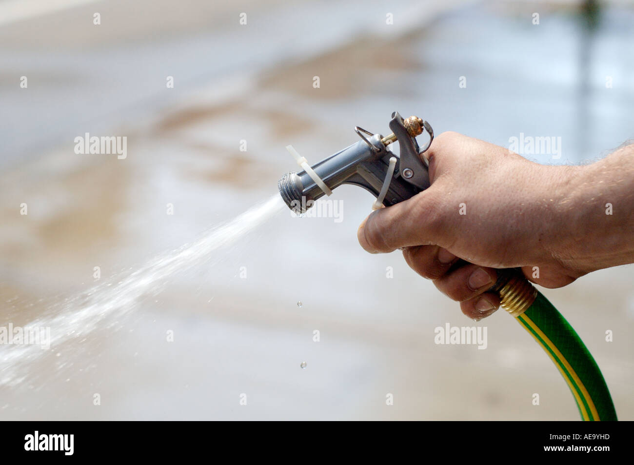 Mans hand spraying water from a garden hose - Stock Image