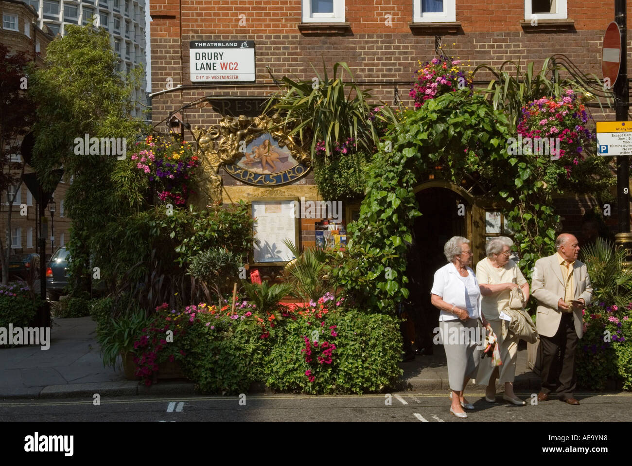 """Covent Garden""  west central London England Three older tourists leave a restaurant in ""Drury Lane"" WC2 Stock Photo"