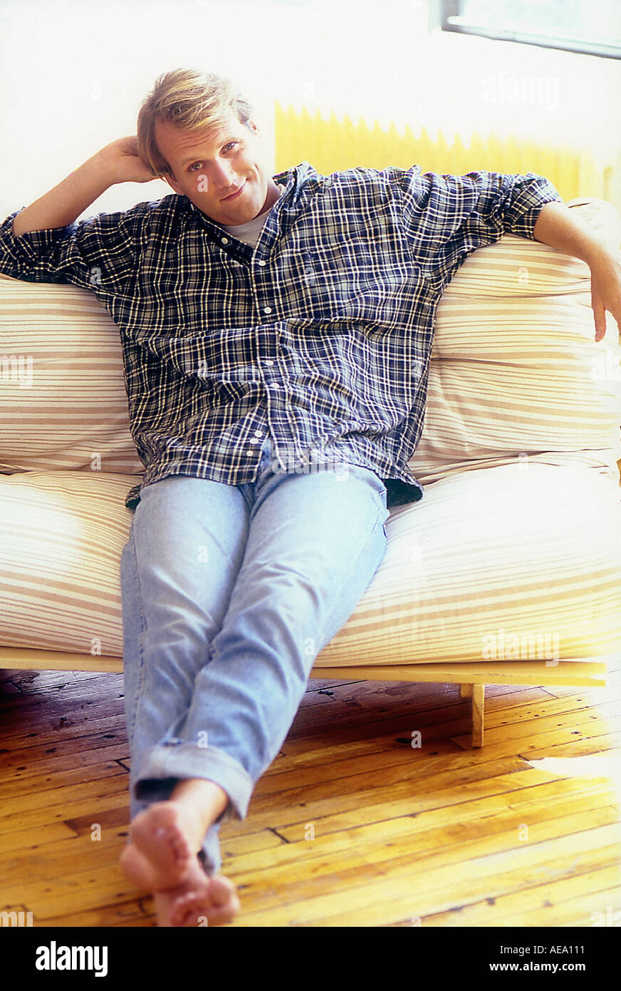 Man sitting on couch smiling - Stock Image