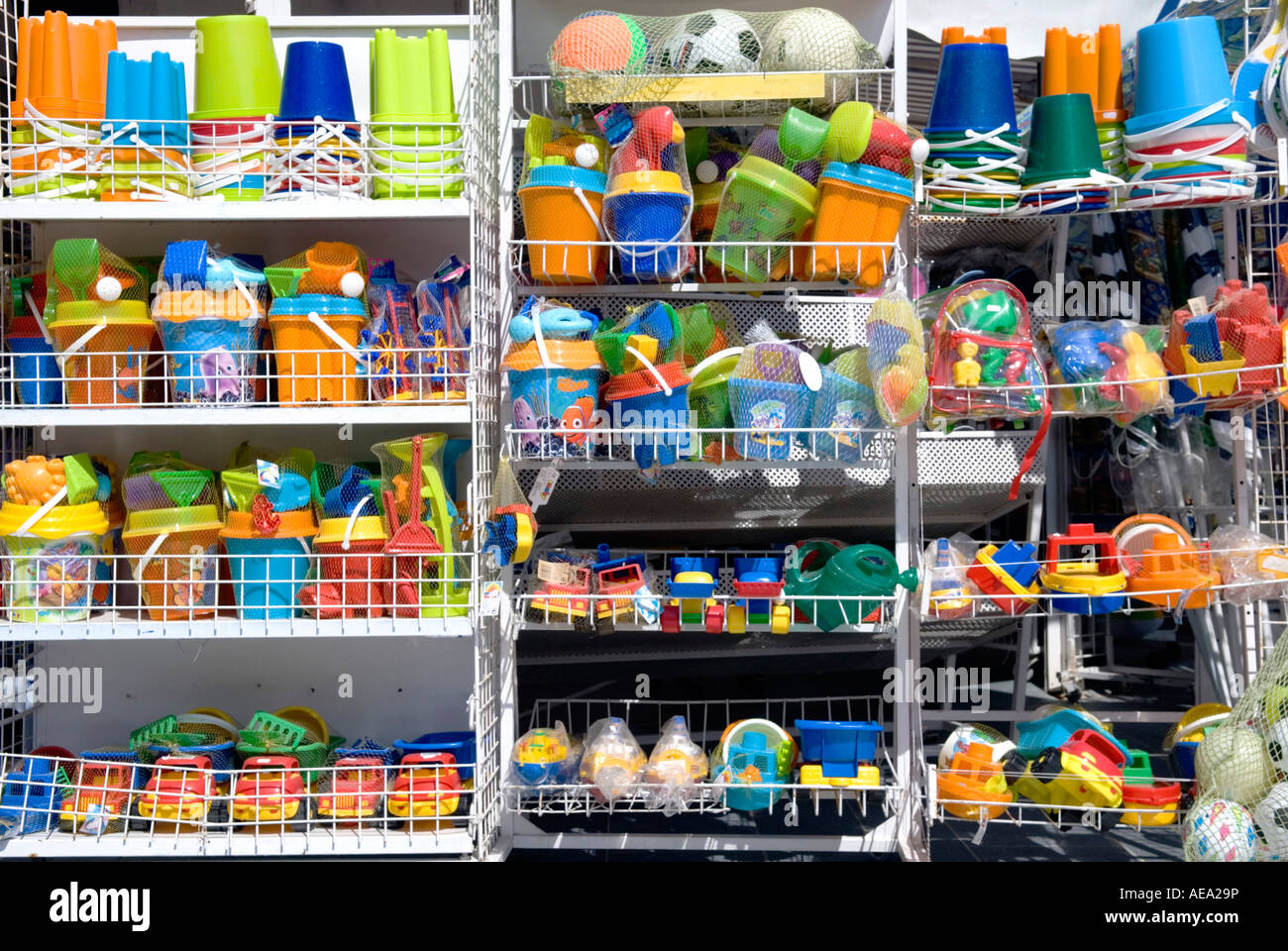 A row of brightly coloured seaside toys on sale outside a tourist gift shop - Stock Image