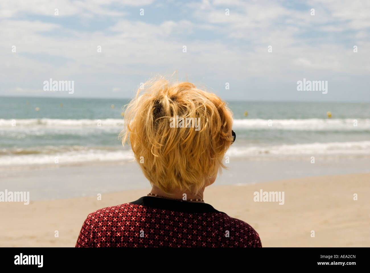 a lone strawberry blonde woman looks away from camera towards the sea and beach - Stock Image