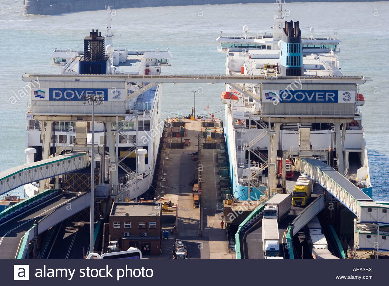 Dover docks, England. High angel shot of ferry terminal, with two ferries and trucks driving on, terminals, Dover - Stock Image