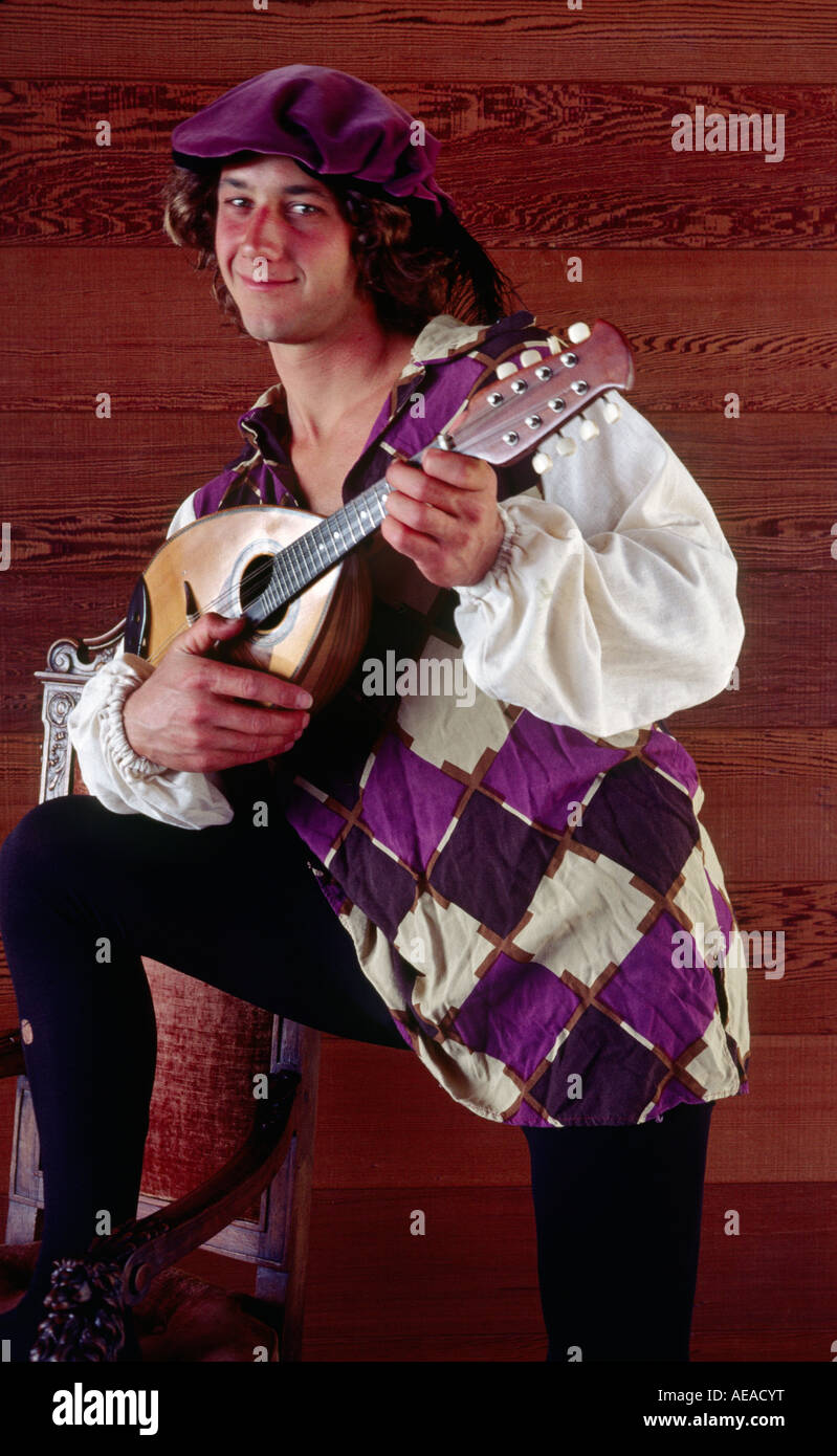 A BARD plays the MANDOLIN dressed in historical clothing MR - Stock Image