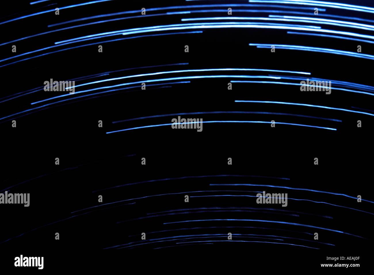 star trail effect blue streaks against black sky - Stock Image