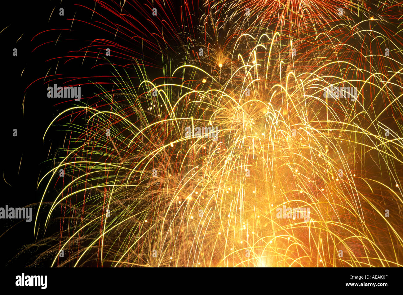 fireworks exploding in black sky close up detail showing many streaks strands explosions - Stock Image