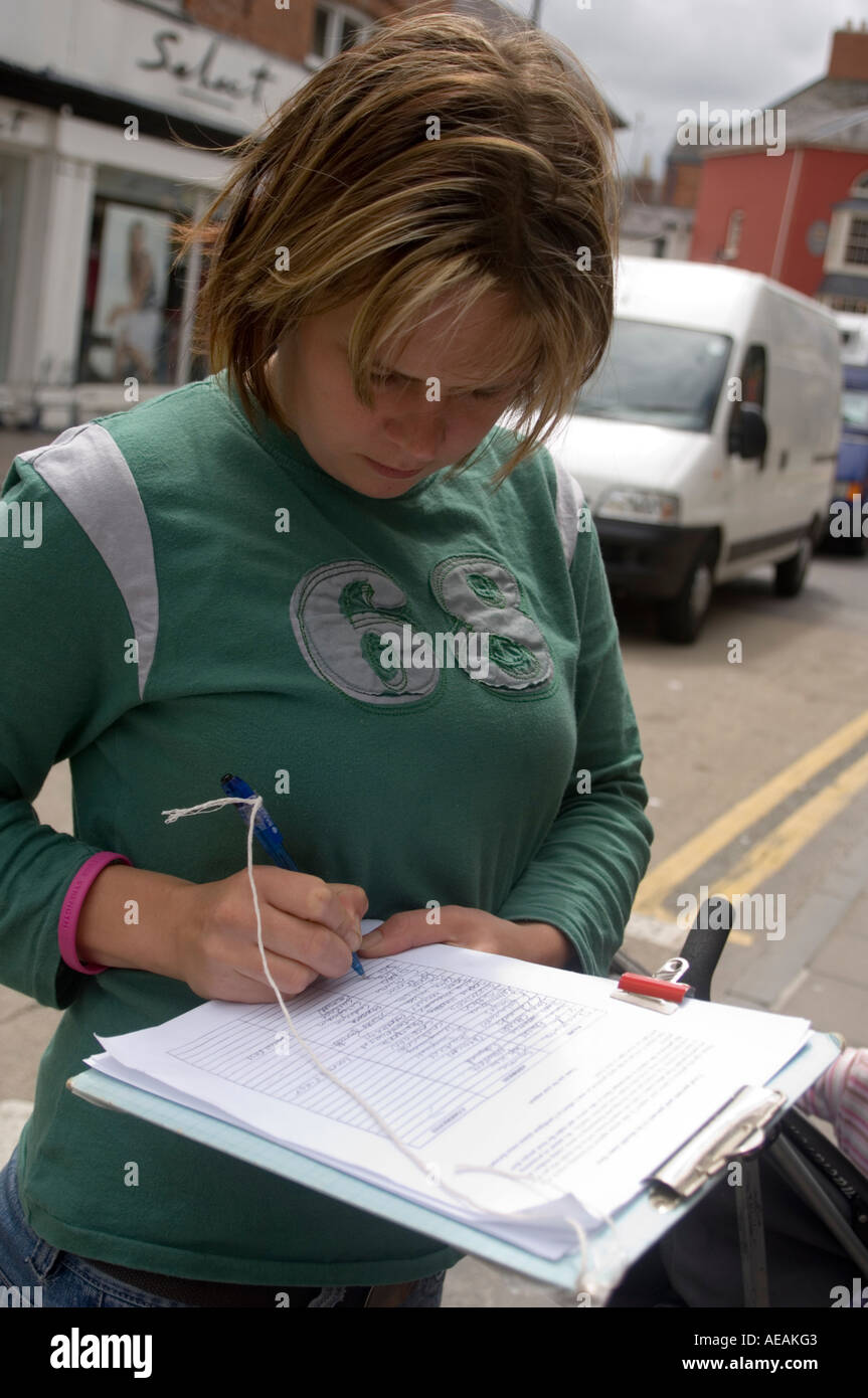 A young mother in Cardigan collecting signatures for petition against giving housing priority to incomers, Wales UK - Stock Image
