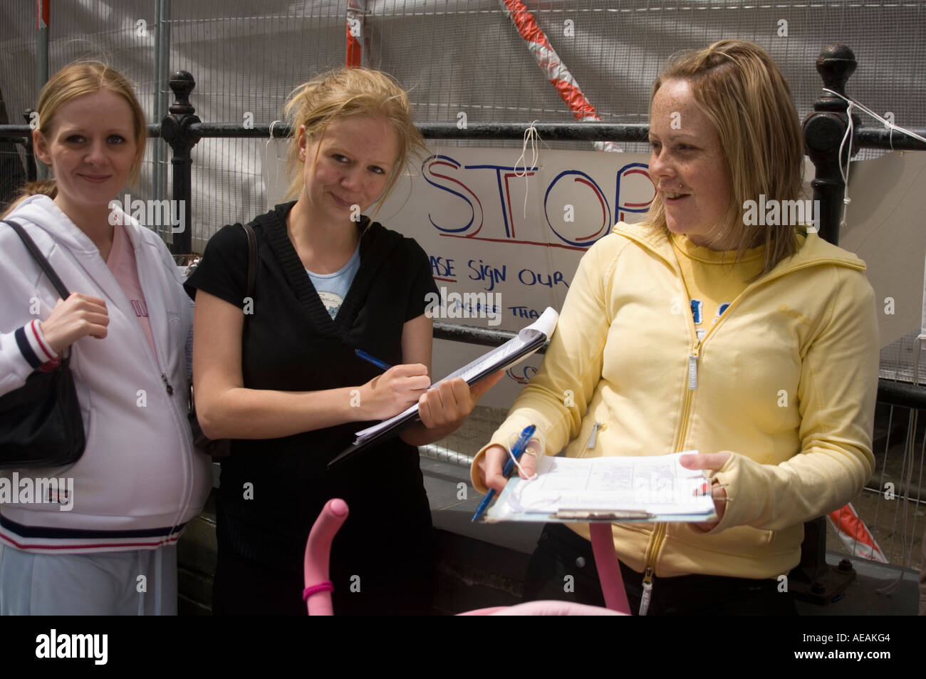 Three young mothers in Cardigan town collecting signatures for petition against giving housing priority to incomers, Wales UK - Stock Image