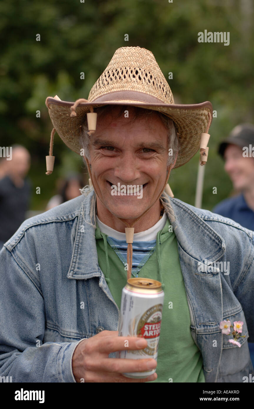 smiling man in his 40s drinking can of lager wearing hat with corks dangling from it - Stock Image