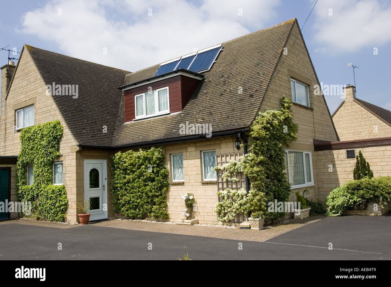 Modern solar thermal hot water panels with evacuated tubes on roof of detached house Cotswolds UK - Stock Image