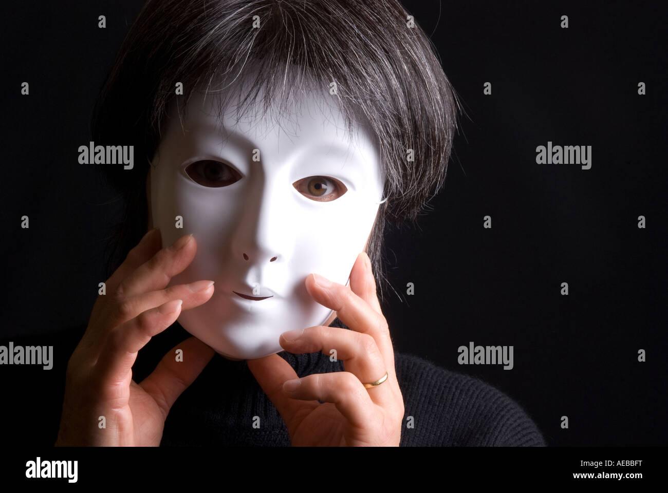 Woman wearing a plain white mask - Stock Image