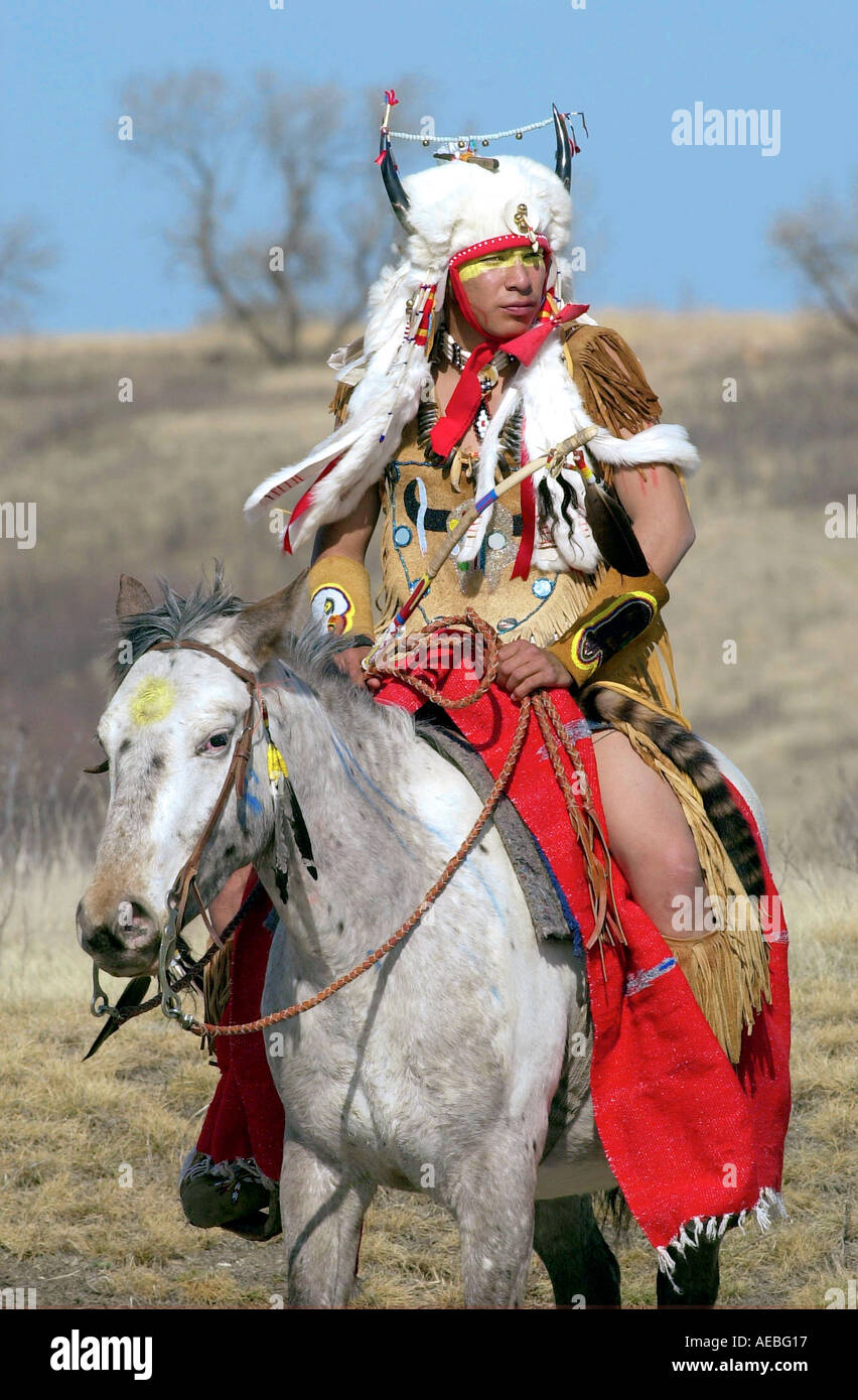 CANADIAN PLAINS INDIAN ON HORSEBACK IN TRADITIONAL COSTUME AND HORNED HEAD DRESS WANUSKEWIN HERITAGE PARK SASKATOON CANADA - Stock Image