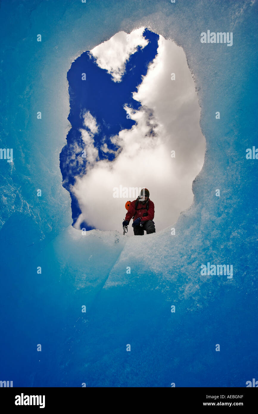 Glacier climber framed by the mouth of a glacier cave, Glaciar Grey Torres del Paine National Park Chile - Stock Image