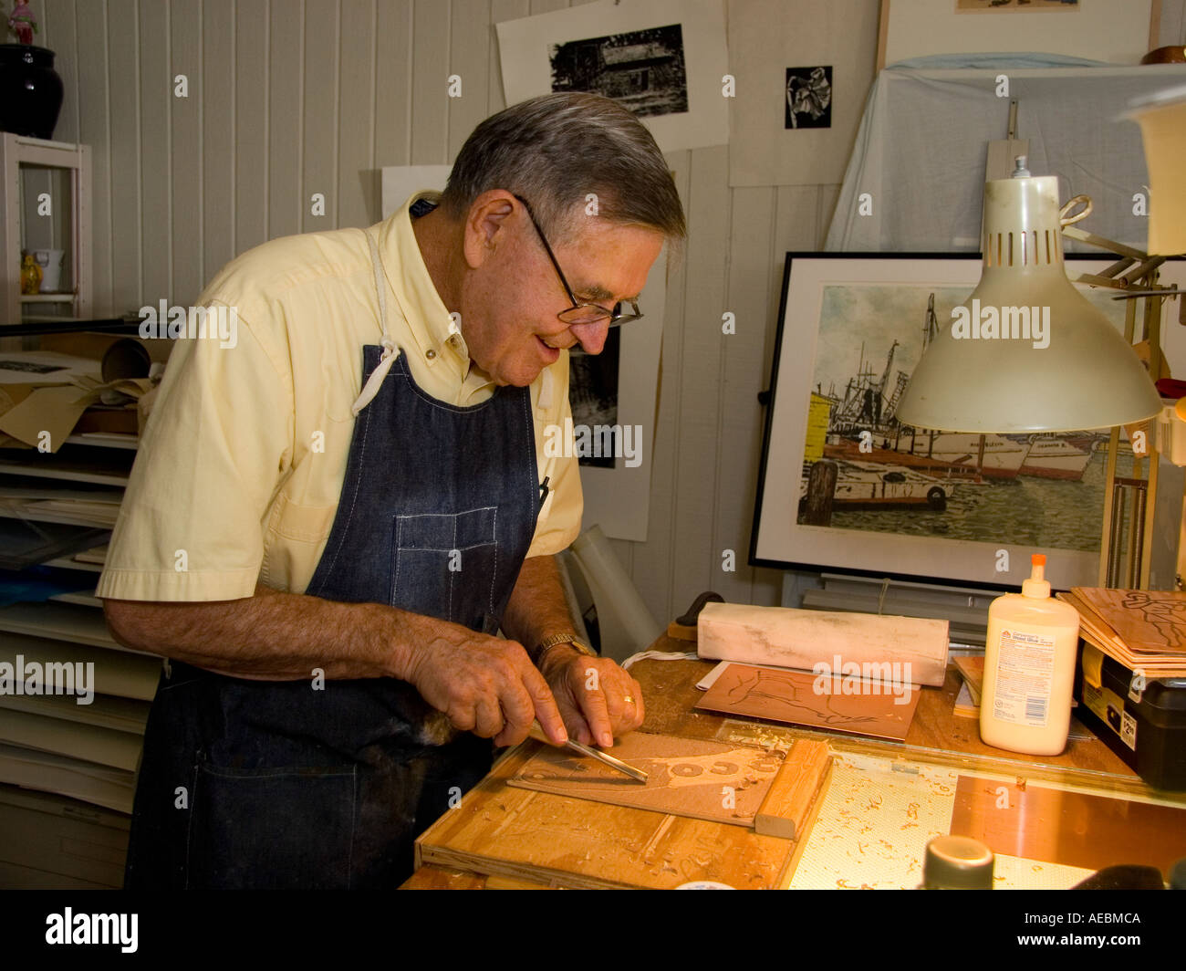 Mature Printmaker at Work, An older male artist creates a woodcut in his studio Stock Photo