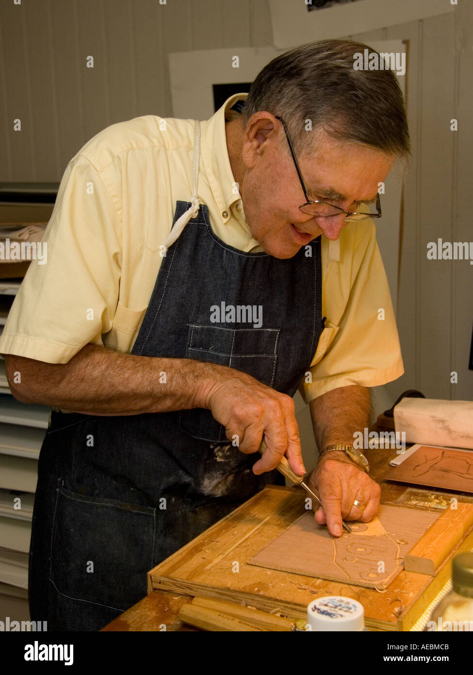Professional Artist Creating a Woodcut, Printmaker works in his studio - Stock Image