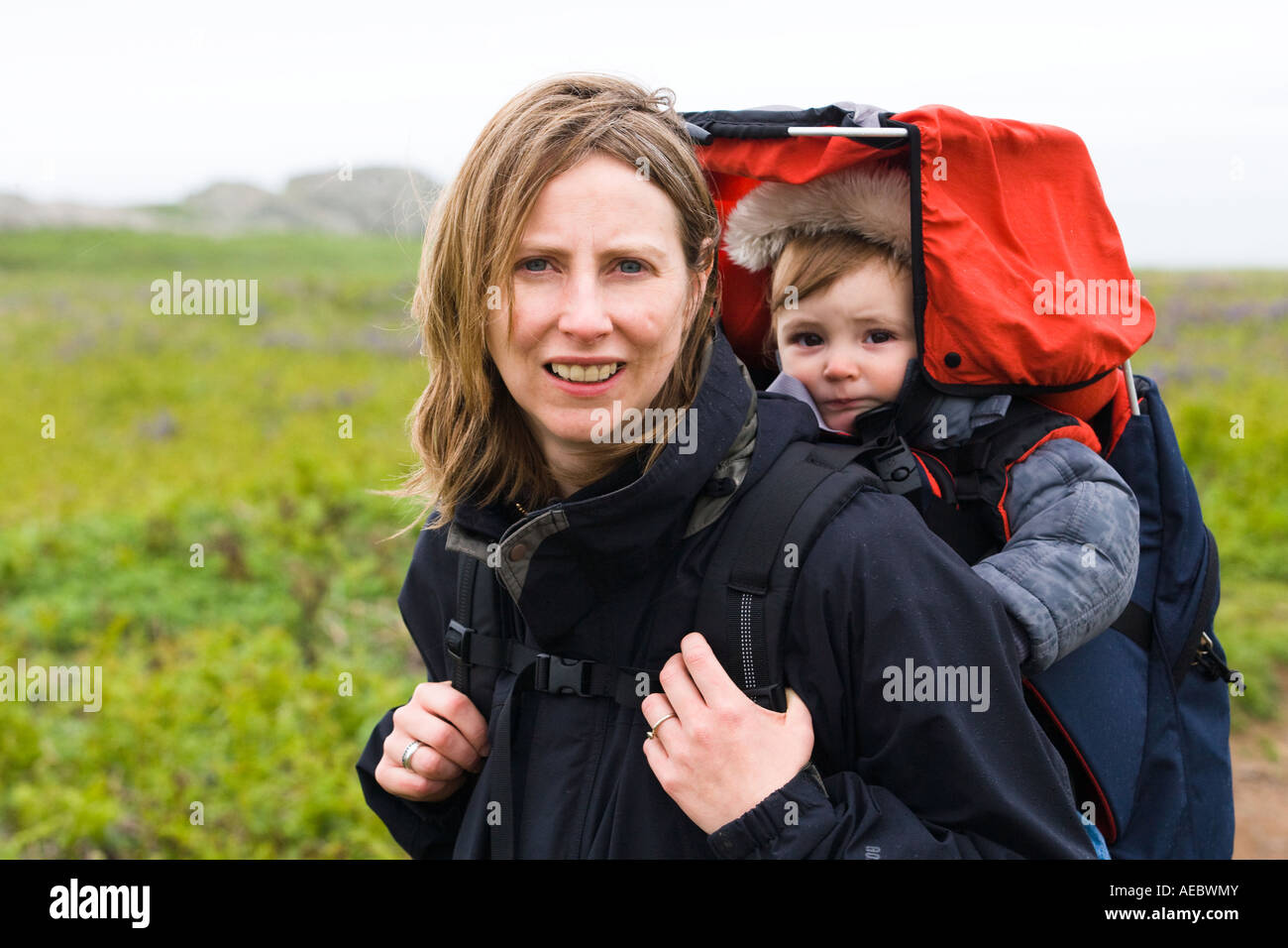 Mother With 10 Month Old Daughter In A Baby Carrier Walking On