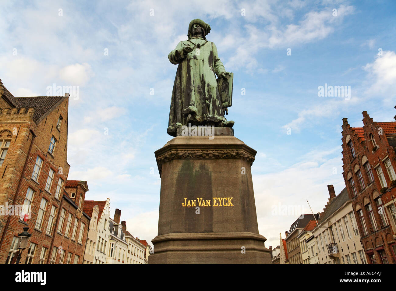 Statue of Jan Van Eyck 1390 1441 a flemish artist with typical buildings in background Bruges Belgium Stock Photo