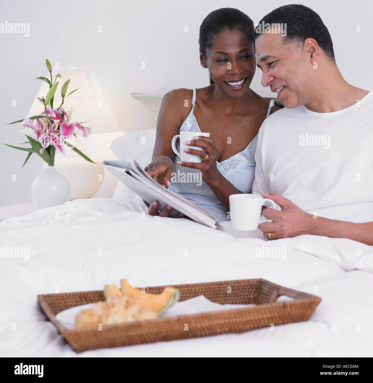 Middle-aged African couple having breakfast in bed Stock Photo