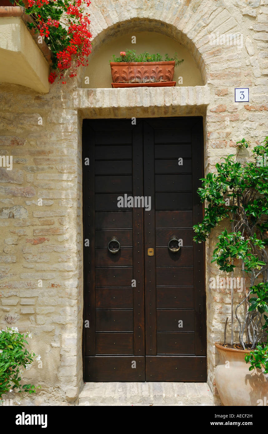 Doorway number 3 with stonework and potted plants in Montefalco Umbria Italy - Stock Image