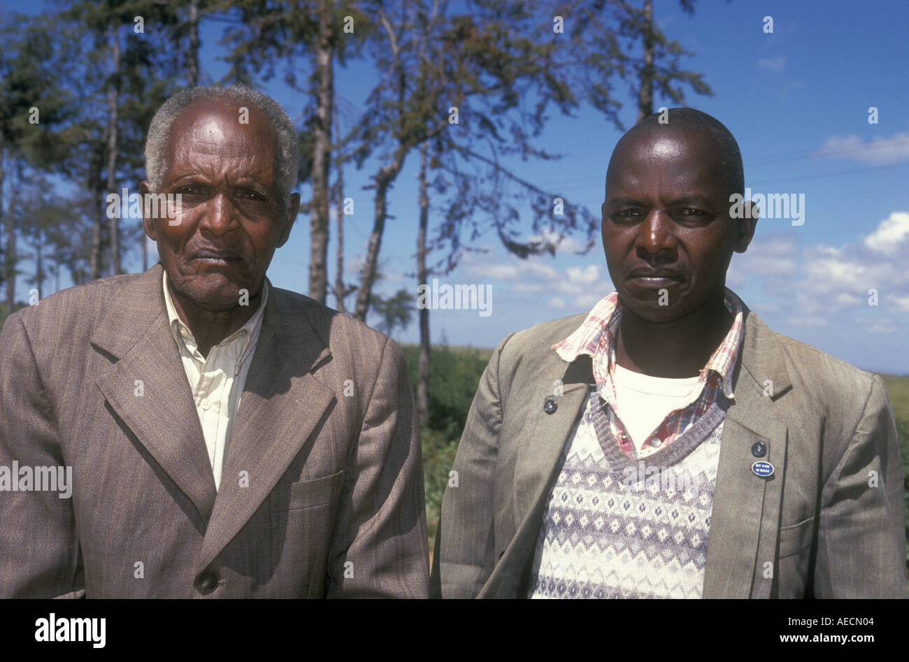 Old Meru man aged 89 years with his son Timau Kenya East Africa The son is wearing a lapel badge reading My God is Real - Stock Image