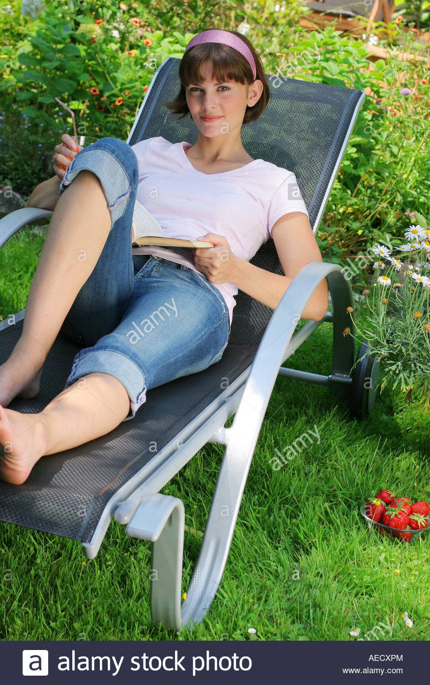 woman lying in the garden on a beach chair - Stock Image