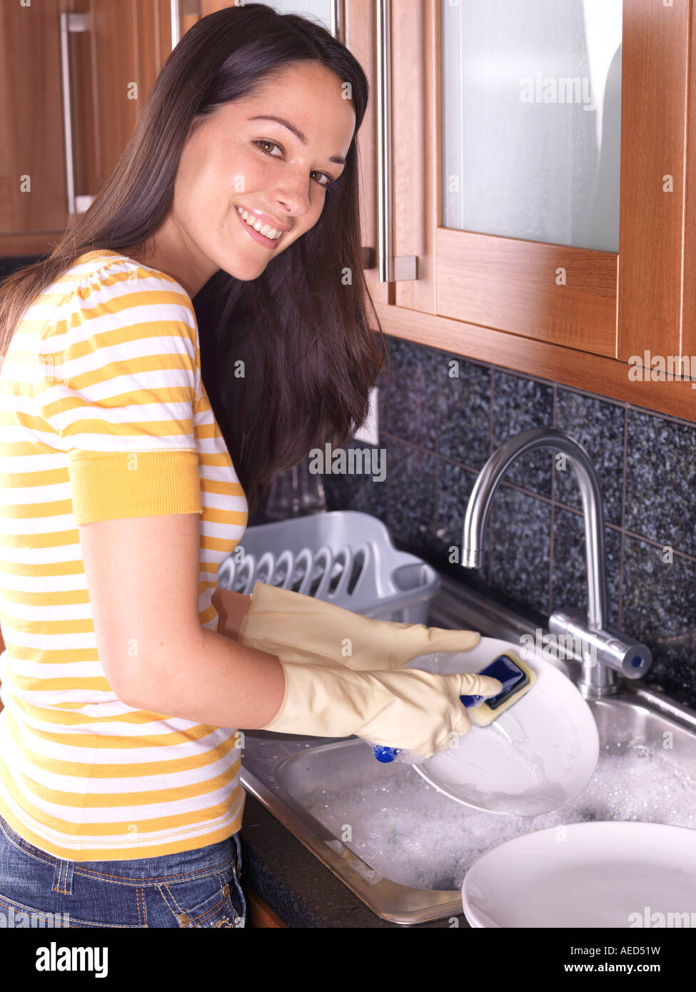 Young Woman Washing Up Dirty Dishes In The Kitchen Sink Alone After A Stock Photo Alamy
