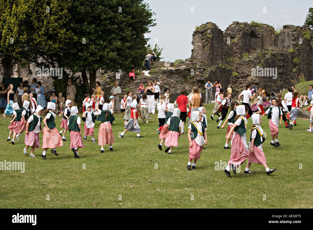 Children in traditional costume country dancing at a festival in a ruined castle grounds Abergavenny Wales UK - Stock Image