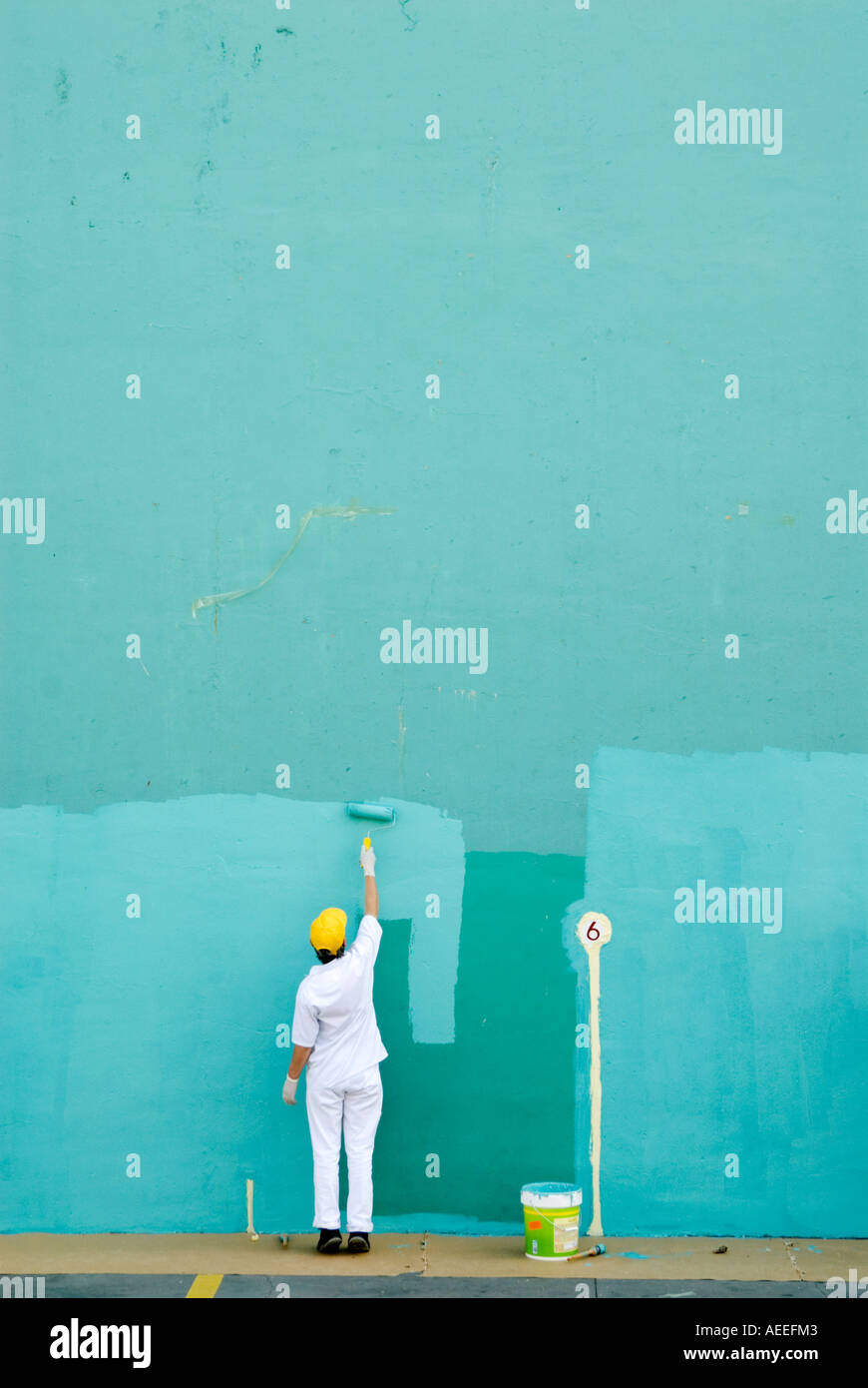 Woman worker painting large blank wall turquoise for game of pelota, Spain - Stock Image