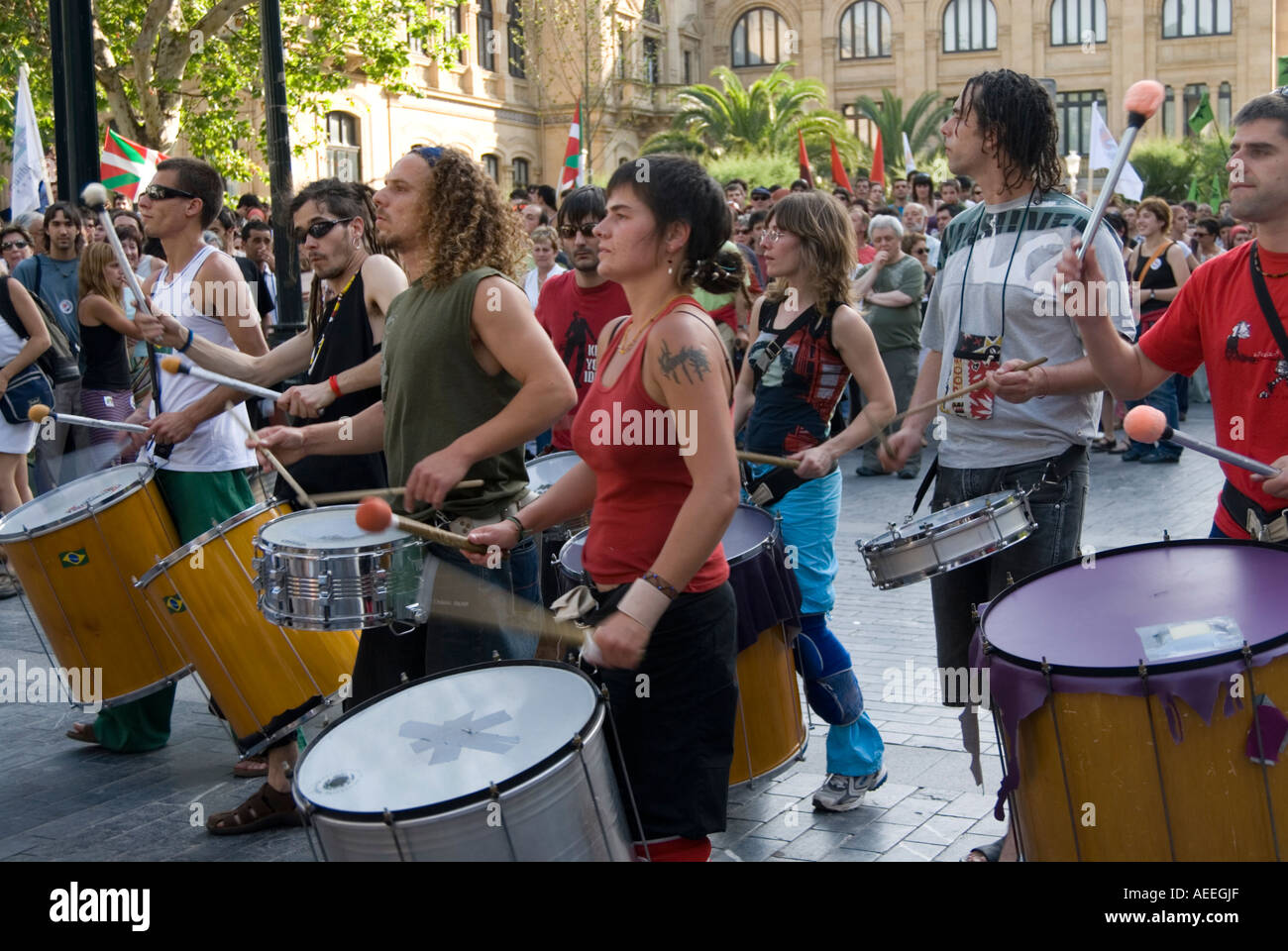 Drummers and percussionists banging drums and making noise at a demonstration, San Sebastian, Spain - Stock Image