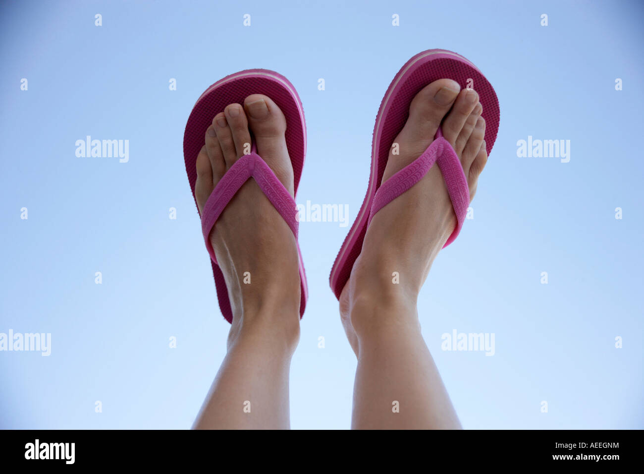 Pair of feet in flip-flops against blue sky - Stock Image