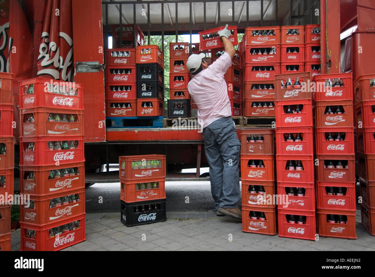 Coca Cola delivery man unloading crates from lorry, Madrid Spain - Stock Image